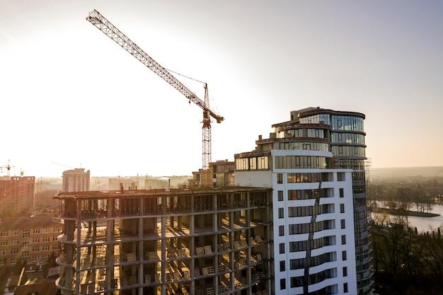 Apartment oder büro hohes gebäude im bau, draufsicht. turmkran und stadtlandschaft bis zum horizont. drohnen-luftaufnahmen.