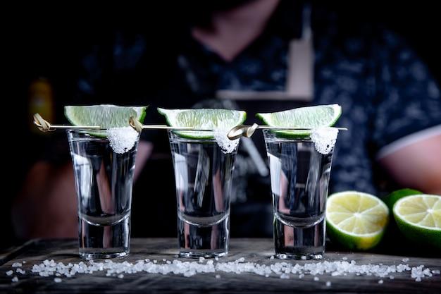 Aperitif mit freunden in der bar, drei gläser alkohol mit limette und salz zur dekoration. tequila-aufnahmen, selektiver fokus