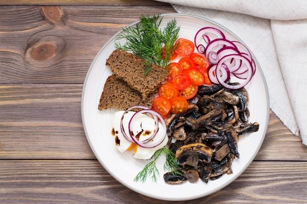 Aperitif von gebratenen pilzen, von zwiebeln, von tomaten und von poschierten eiern auf einer platte auf einem holztisch