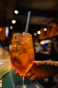 Aperol spritz cocktail alkoholisches getränk auf barthekenbasis mit eiswürfeln und orangen.