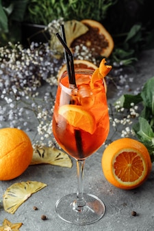 Aperol spritz cocktail auf einem grauen betontisch. ein glas aperol spritz mit orangenscheiben. sommercocktail im glas