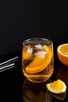 Aperol spritz cocktail im glas auf dem schwarzen hintergrund