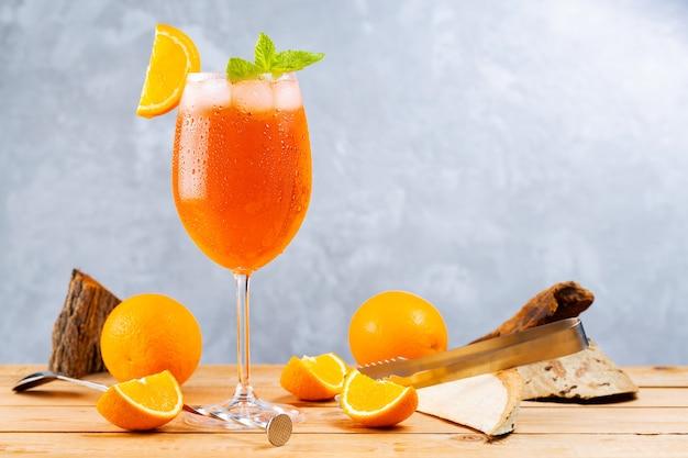 Aperol spritz cocktail mit barzubehör. italienischer aperol-spritz-cocktail und eine in scheiben geschnittene orange auf grauem hintergrund. cocktail aperol spritz mit frischer minze