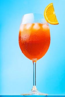 Aperol-spritz-cocktail mit einer orangenscheibe. glas cocktail aperol spritz auf blauem grund. italienischer sommercocktail im stil des minimalismus. vertikale ausrichtung