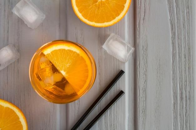 Aperol-spritz-cocktail oder orangencocktail im glas auf dem grauen hölzernen hintergrund. draufsicht. speicherplatz kopieren.