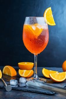 Aperol spritz cocktail- und barzubehör. italienischer aperol-spritz-cocktail und eine in scheiben geschnittene orange auf dunklem hintergrund. sommercocktail aperol spritz auf einer schiefertafel
