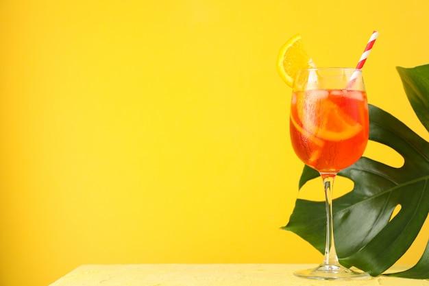 Aperol spritz cocktail und palmblatt auf gelbem hintergrund