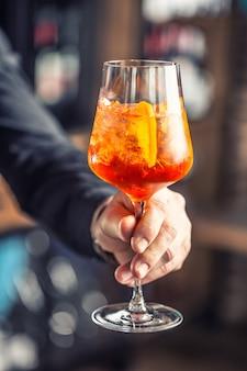 Aperol-spritz-getränk. barkeeper-hand, die glas mit aperol spritz-getränk hält.