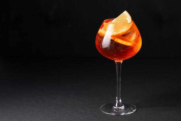 Aperol spritz in einem glas mit eis und orange