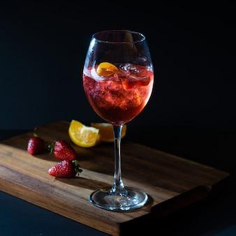 Aperol spritz roter aperitif-cocktail im glas mit eis auf schwarzem hintergrund