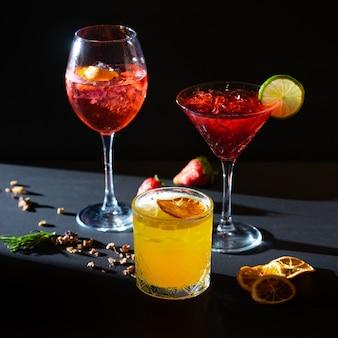 Aperol spritz und rote und gelbe aperitif-cocktails im glas mit eis auf schwarzem hintergrund