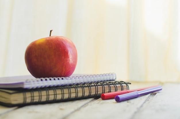 Apfel auf notizblock mit bleistiften