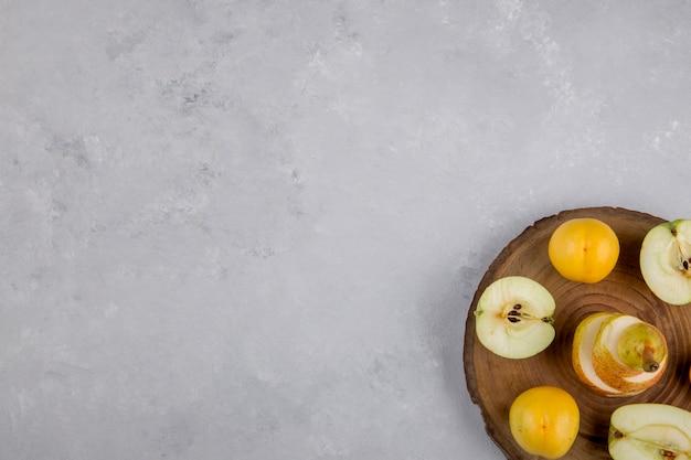Apfel, birne und pfirsiche auf einem stück holz, draufsicht