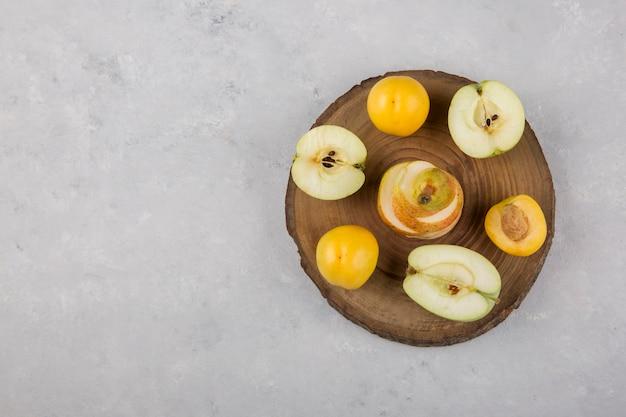 Apfel, birne und pfirsiche in einem hölzernen herzstück