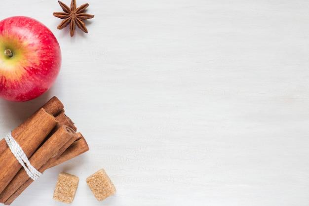 Apfel, brauner zucker und anis mit zimt auf hellem hintergrund