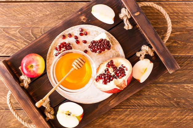 Apfel, granatapfel und honig auf einem hölzernen tablett-draufsicht. traditionelles essen des jüdischen neujahrsfestes - rosh hashana.