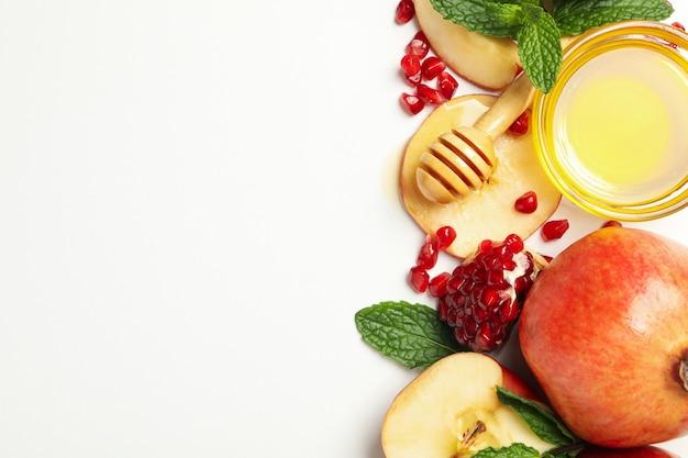 Apfel, granatapfel und honig auf weiß. behandlung zu hause