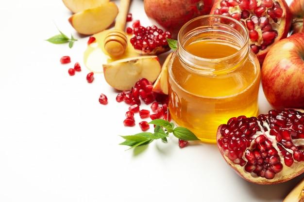 Apfel, granatapfel und honig auf weiß, nahaufnahme. behandlung zu hause
