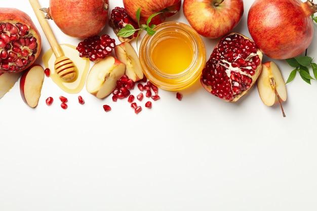 Apfel, granatapfel und honig auf weißer draufsicht. behandlung zu hause