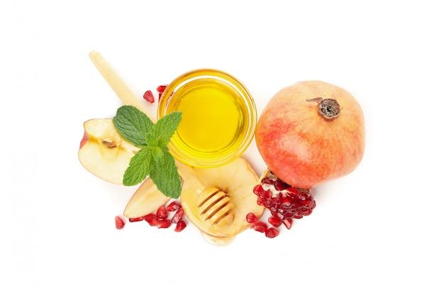 Apfel, granatapfel und honig isoliert auf weiß. natürliche behandlung