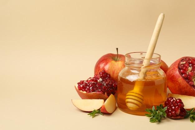 Apfel, honig und granatapfel auf beige. behandlung zu hause