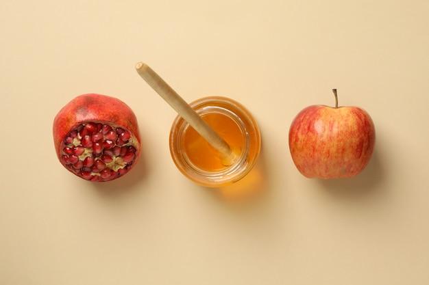 Apfel, honig und granatapfel auf beige, draufsicht. behandlung zu hause