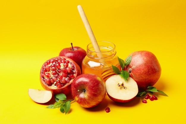 Apfel, honig und granatapfel auf gelb. behandlung zu hause