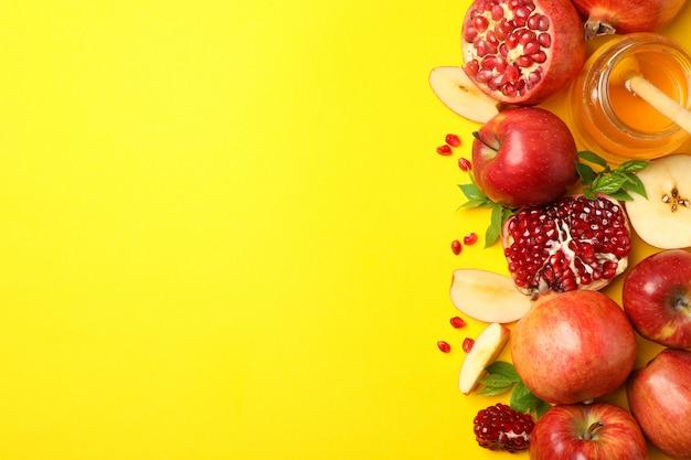 Apfel, honig und granatapfel auf gelb, platz für text