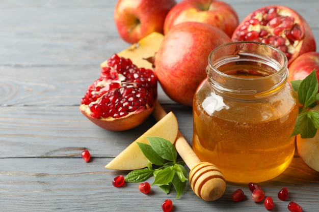 Apfel, honig und granatapfel auf holz, nahaufnahme. behandlung zu hause