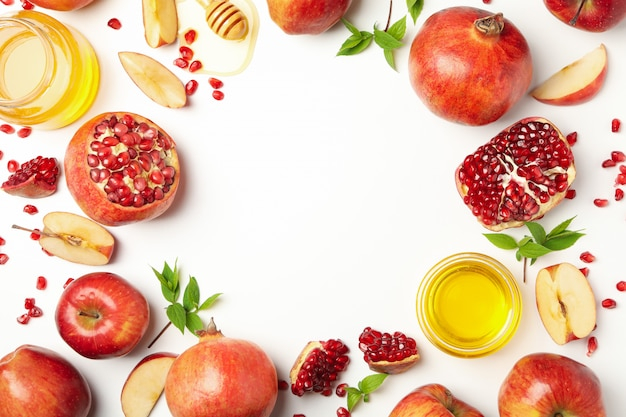 Apfel, honig und granatapfel auf weiß, platz für text