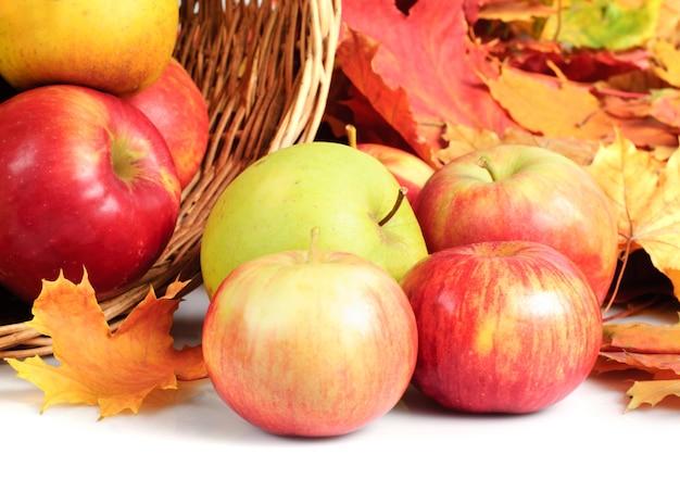Apfel im korb, der auf weißem hintergrund verstreut