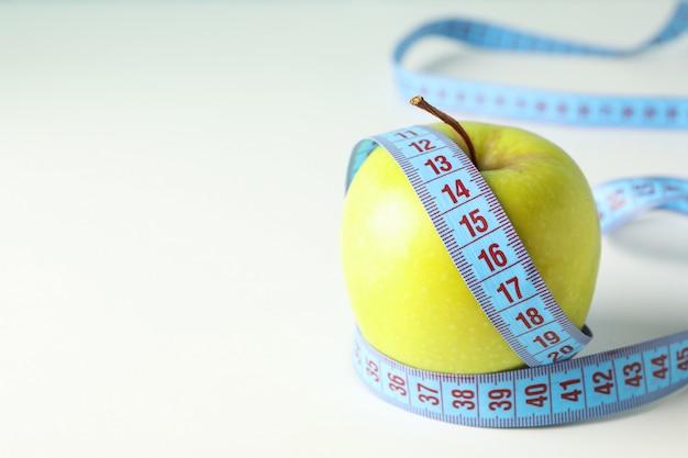 Apfel mit maßband auf weißem hintergrund, nahaufnahme