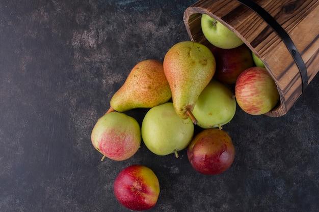 Apfel, pfirsich und birnen aus einem holzeimer