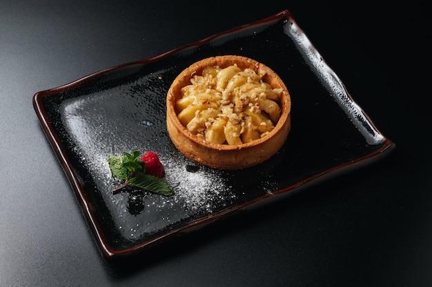 Apfel-törtchen-nachtisch hausgemachter shortbread-minitörtchen-kuchen auf schwarzem hintergrund