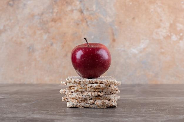 Apfel und ein haufen puffreiskuchen auf der marmoroberfläche