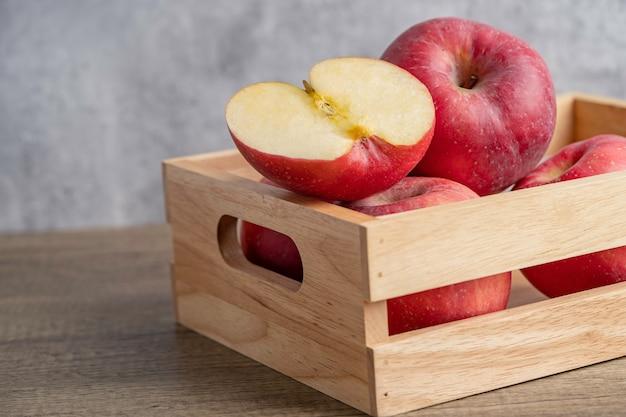 Apfel und halbe frucht in holzkiste mit kopienraum.