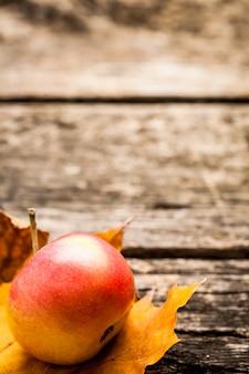 Apfel- und herbstblatt auf altem holztisch