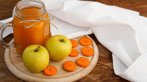 Apfel- und karottensaft im glas, frisches gemüse und obst auf hölzernem hintergrund. rustikaler stil. hausgemachtes getränk mit vitaminen