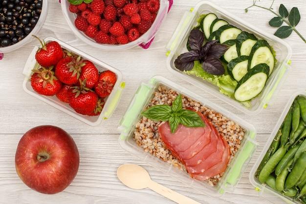 Apfel- und plastikbehälter für die zubereitung von mahlzeiten mit frischen erdbeeren, himbeeren, buchweizenbrei.