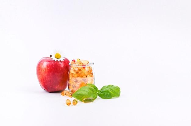 Apfel und vitamine in kapseln copyspace. medikamente und medikamente für die gesundheit