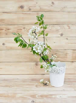 Apfelbaumblumen stehen in einer weißen vase auf einem hölzernen hintergrund