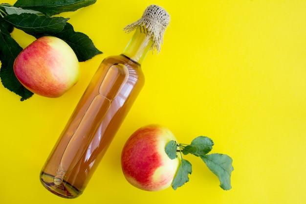 Apfelessig apfelwein in der glasflasche auf dem gelben hintergrund