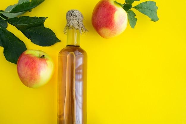 Apfelessig apfelwein in der glasflasche auf dem gelben tisch. draufsicht. kopierraum.