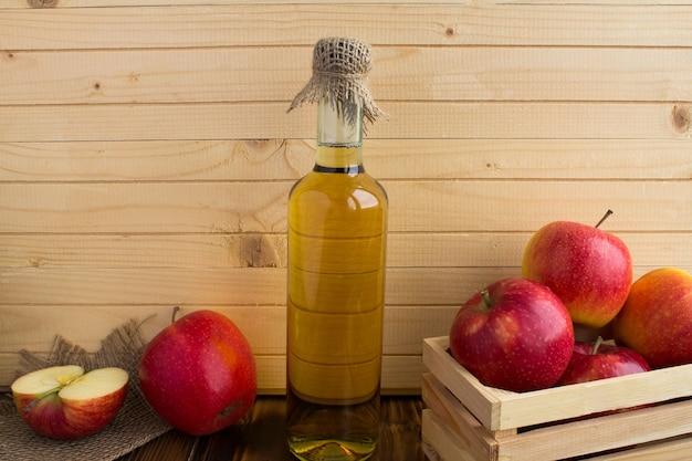 Apfelessig-apfelwein in der glasflasche auf dem hellbraunen hölzernen hintergrund