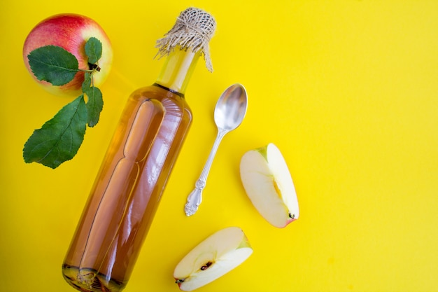 Apfelessig apfelwein in der glasflasche auf der gelben oberfläche.