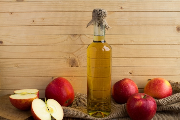 Apfelessig apfelwein in der glasflasche auf der hellbraunen holzwand