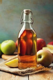 Apfelessig. flasche organischer essig oder apfelwein des apfels auf hölzernem hintergrund. gesundes bio-essen.