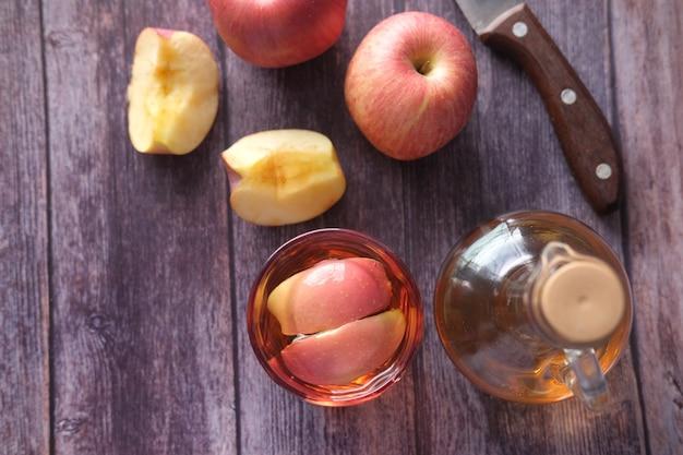 Apfelessig im glas mit frischem apfel auf tischplattenansicht