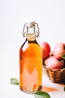 Apfelessig in einer flasche auf weißem holztisch mit äpfeln in einem korb.