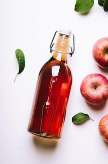 Apfelessig in einer flasche auf weißem holztisch mit äpfeln und blättern. rustikaler stil.